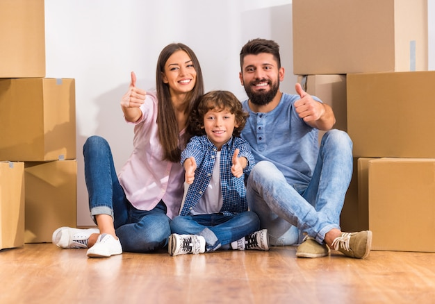 若い幸せな家族が新しい家に移動し、ボックスを開きます。