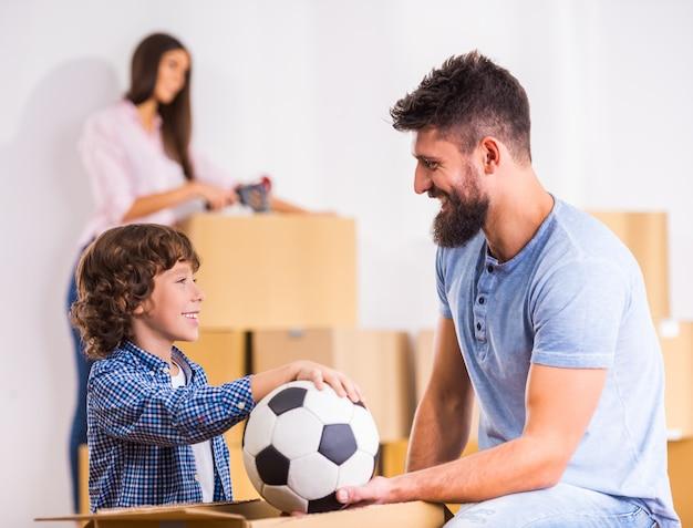 幼い息子と彼のお父さんはサッカーボールを保持しています。