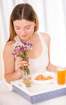 彼の寝室で朝食を食べる若い幸せな女。