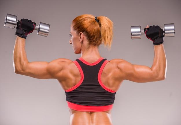 アスレチックの女性はダンベルで筋肉をポンピングしています。