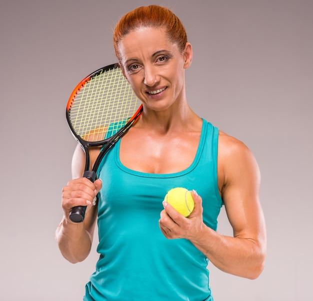 中年スポーツ女性はテニスラケットでポーズします。