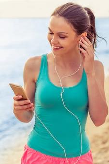 スポーツ服とイヤホンの女の子は音楽を聴いています。
