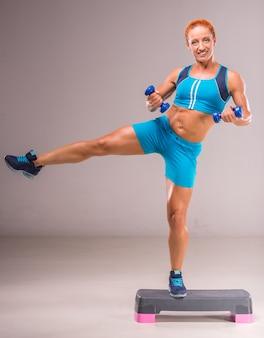 女性はステップボードにダンベルで運動をしています。