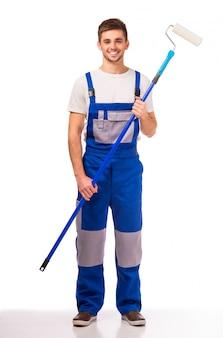 部屋の壁を塗る作業服の男。
