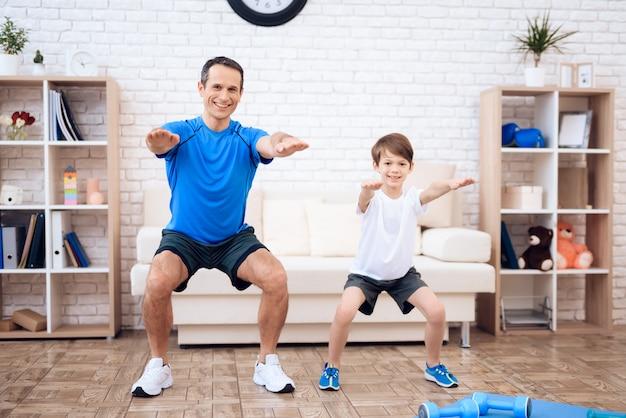Счастливый отец и сын делают разминку делать приседания в домашних условиях.