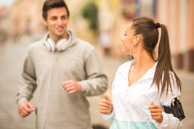 屋外を実行する若い幸せなカップル。