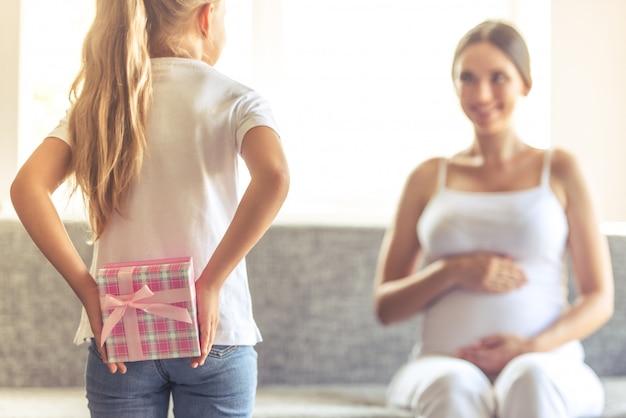 Маленькая девочка держит подарок за спиной для своей мамы.