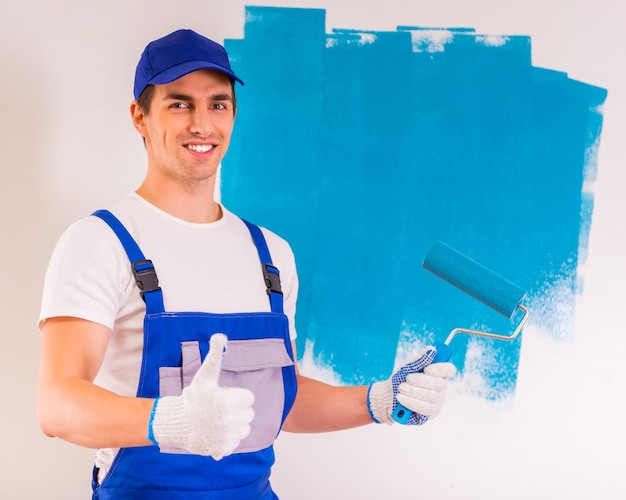 男性画家は壁を塗って親指を表示します。
