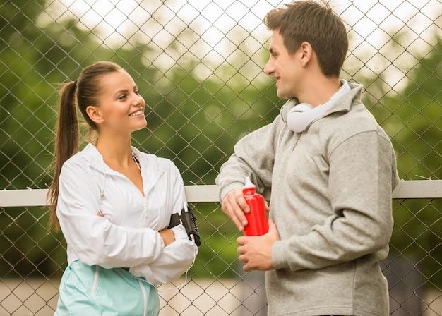 Молодые люди в спортивной одежде отдыхают и разговаривают.