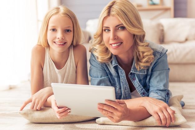 Дочь с помощью планшета, глядя на камеру и улыбается.