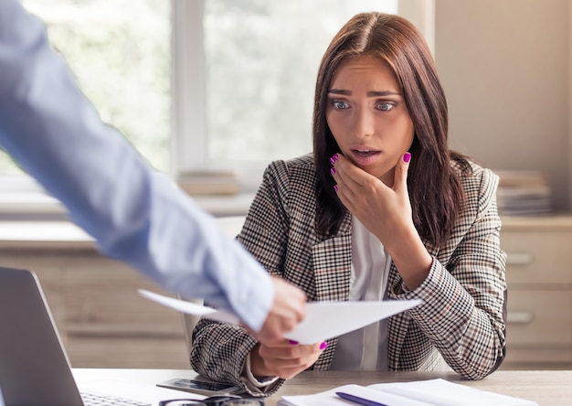 スタイリッシュなフォーマルな服を着た女性は、文書を撮ってショックを受けています。