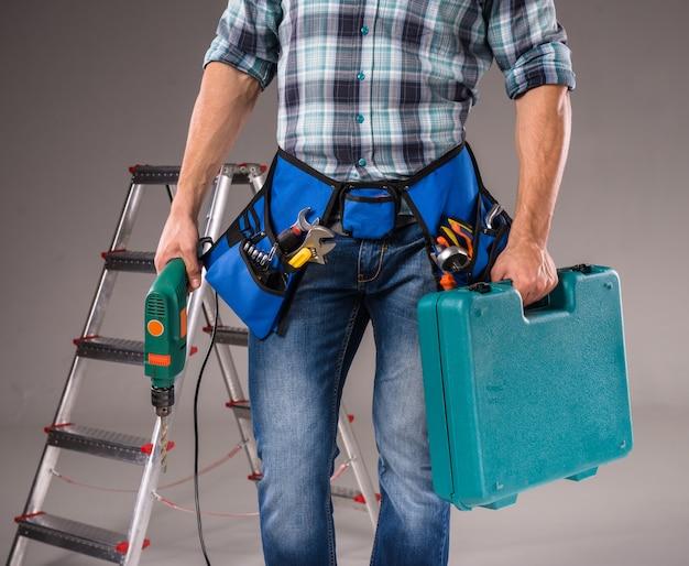 男は道具を持って立っています