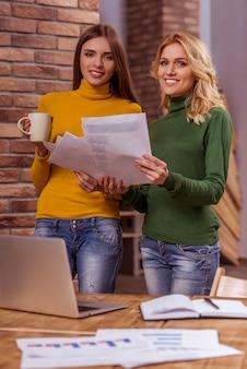 Две красивые молодые девушки держат чашку и документы.