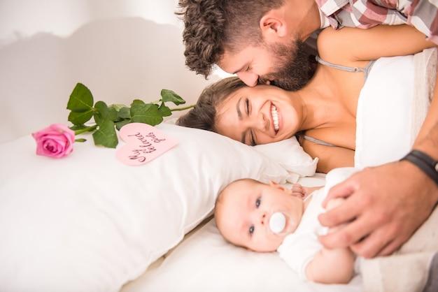 自宅のベッドで赤ちゃんを持つ親。