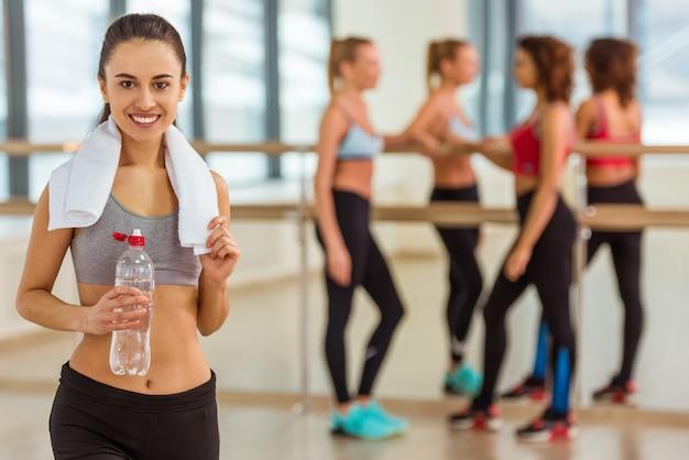 女の子は正面を見て、水のボトルを保持しています。