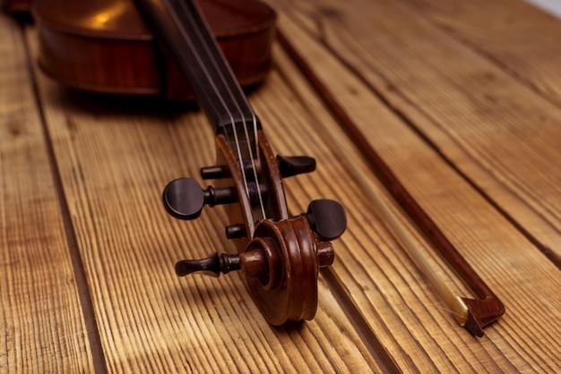 ヴァイオリンは木製のテーブルの上に横たわっています。