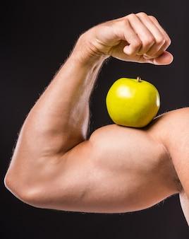 彼の完璧な上腕二頭筋を示す筋肉の男のクローズアップ。