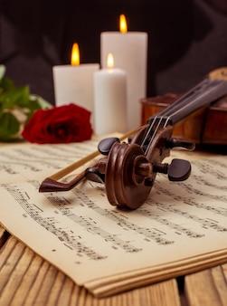 ヴァイオリンとノートは木製テーブルの上に横たわって閉じます。