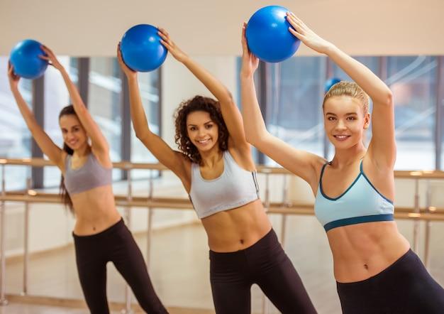 Спортивные девушки улыбаются во время тренировки с фитнес-мячом.