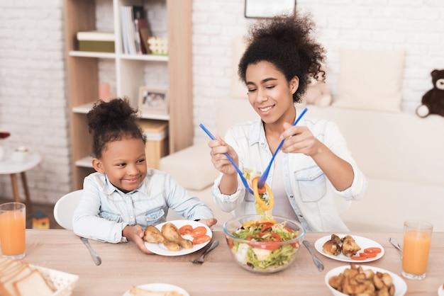 ママと娘は台所で一緒に食べます。