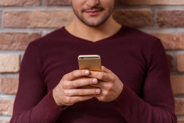 男はレンガの壁に立っている間携帯電話を使用しています。