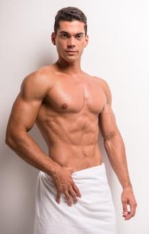 上半身裸の若い男はタオルで覆われています。