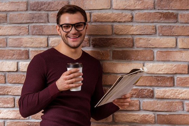 カジュアルなセーターとカップを保持している眼鏡のビジネスマン。