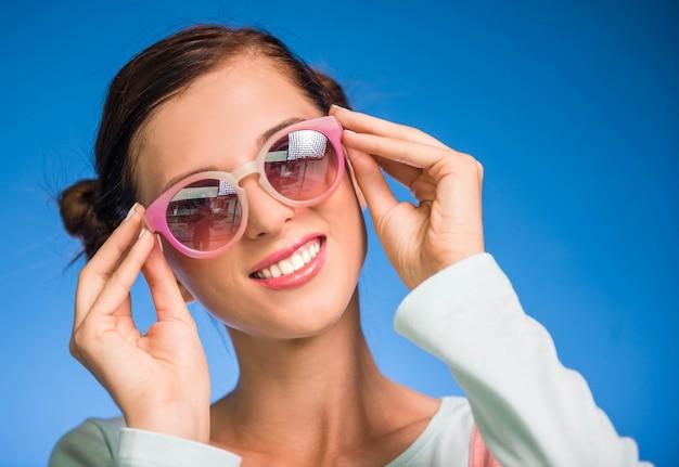 若い女性はファンキーなメガネで楽しんでいます。