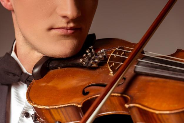 男は首にバイオリンをかけて演奏します。