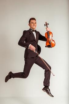 若いミュージシャン男演奏ヴァイオリンとジャンプ。