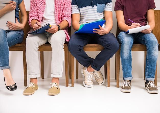 インタビューを待っている椅子に座っている人々のグループ