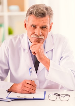 彼のオフィスに座っている青いリボンを持つ医師の肖像画。