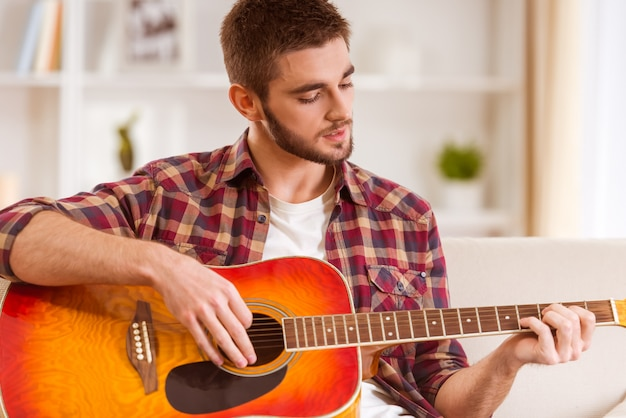 自宅でギターを弾く若い男の肖像画。