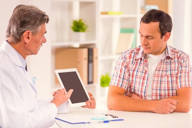 医者は患者に何かをタブレットで見せます。