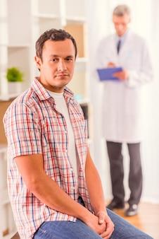 男が診療所に座って正面を見る。