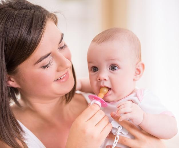 若いママは彼女の赤ちゃんにおしゃぶりを与えます。