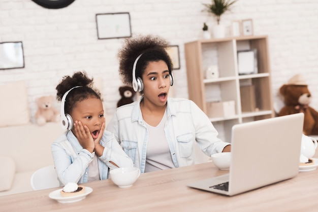 Мама и дочь смотрят что-то на ноутбуке.