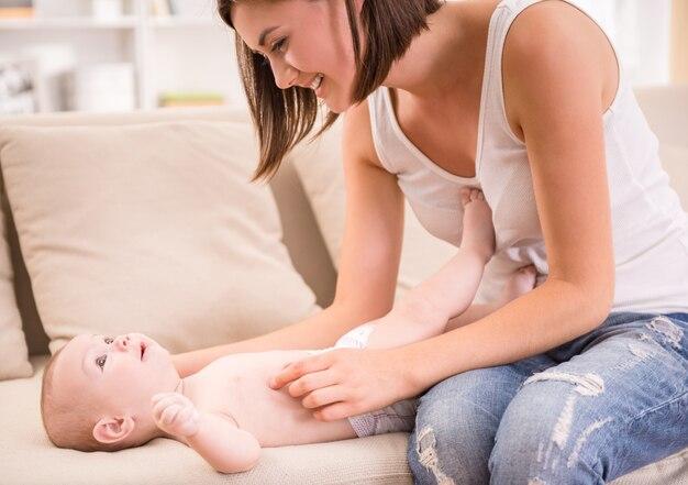 彼女の母親と一緒にソファに横たわってかわいい女の子。