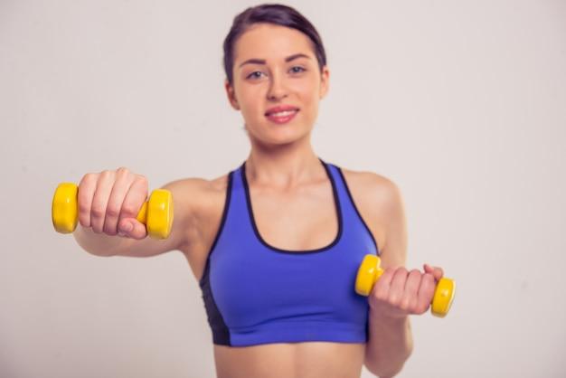スポーツウェアの魅力的な若い女性はダンベルを保持しています。
