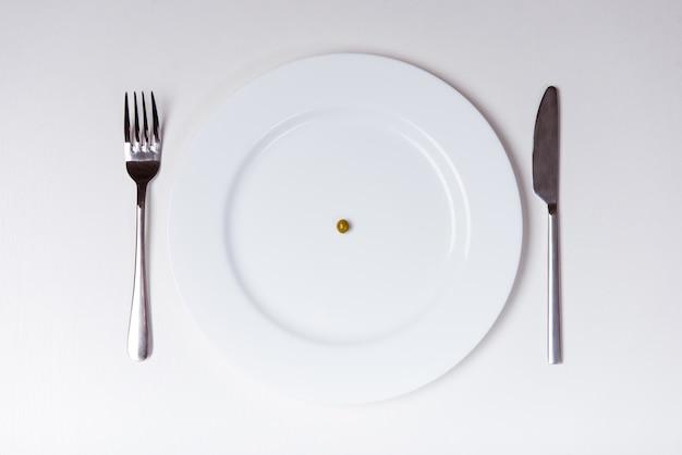 Белая тарелка с вилкой и ножом лежа