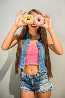 女性は彼女の目にドーナツを押しながら笑みを浮かべて。