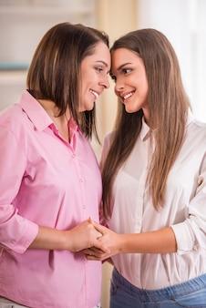 Мама и дочка стоят вместе в квартире.