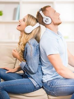 美しいカップルは、ヘッドフォンで音楽を聴きます。