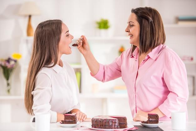 母とデザートを食べるために自宅で十代の娘。