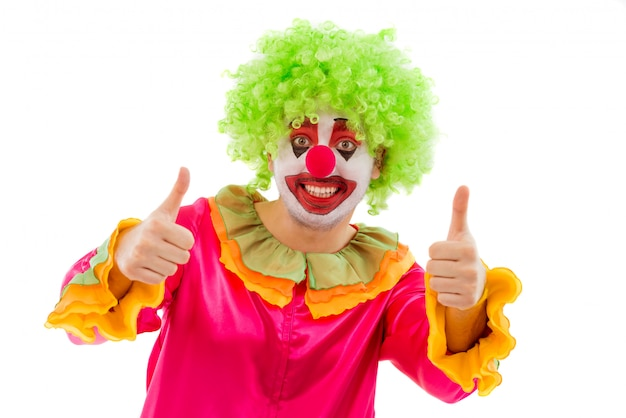 Портрет смешного клоуна в зеленом парике показывая одобренный знак.