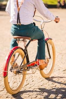 シャツとサスペンダーを着た男が自転車に座っています。