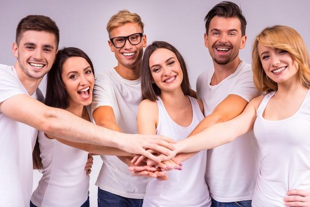 陽気な人々は一緒に立ち、手をつないでいます。