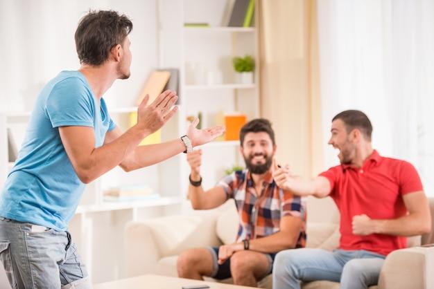 若い幸せな男性の友人は家で楽しい時を過します。