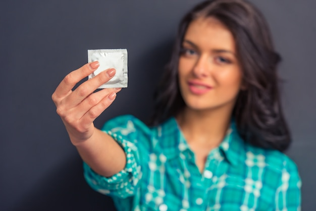 コンドームを持つ魅力的な若い女性。