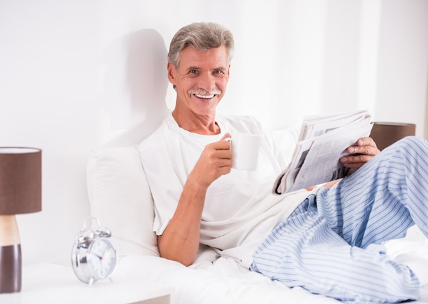 コーヒーのカップを持つシニア男はベッドで新聞を読んでいます。